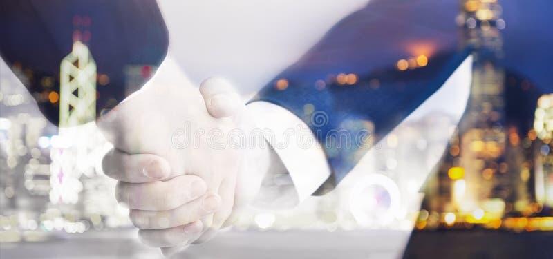 2 бизнесмена тряся руки на расплывчатой предпосылке стоковые фото
