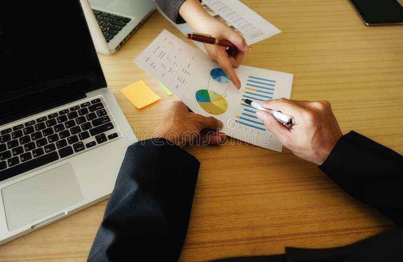 Бизнесмены Азии обсуждая диаграммы и диаграммы показывая результаты их успешной сыгранности стоковые фотографии rf
