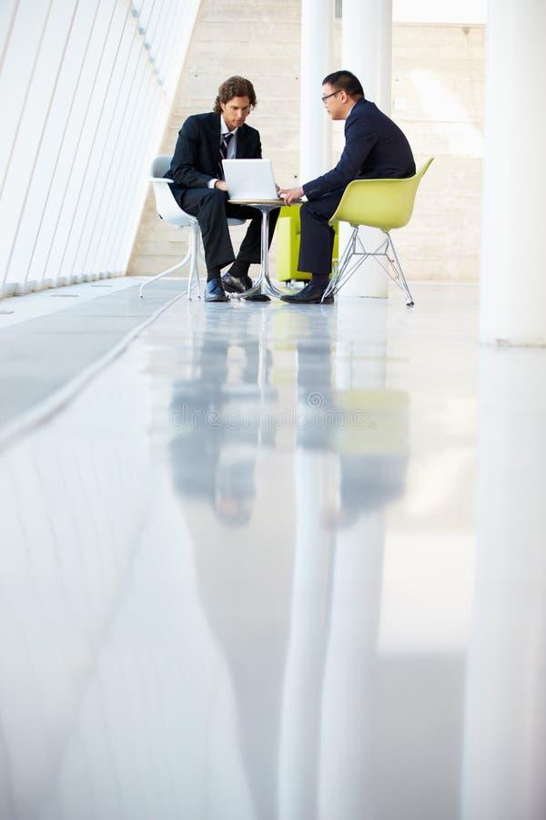 Бизнесмены встречая компьтер-книжку в самомоднейшем офисе стоковые фото
