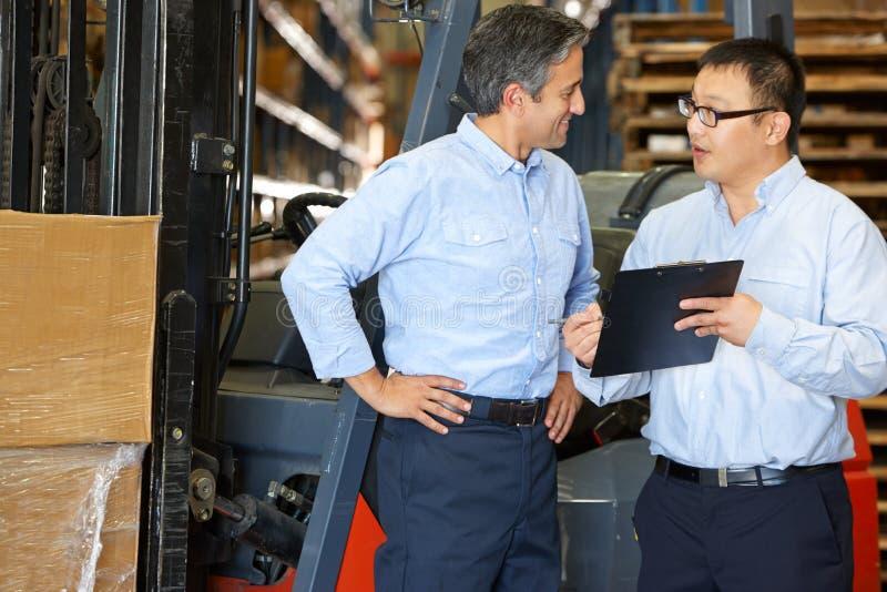 Бизнесмены встречая платформой грузоподъемника в пакгаузе стоковое изображение
