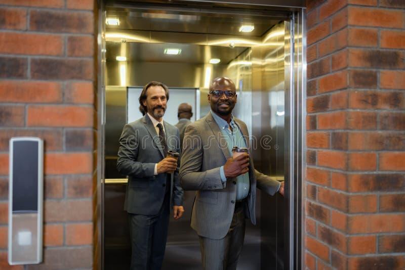 Бизнесмены входя в лифт в утро держа на вынос кофе стоковое фото rf
