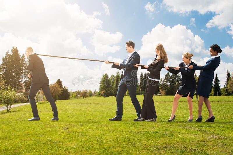Бизнесмены вытягивая веревочку в противоположном направлении стоковая фотография