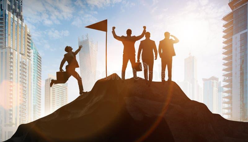 Бизнесмены в достижении и концепции сыгранности стоковое изображение