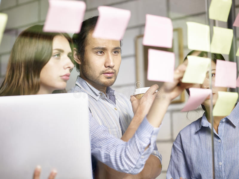 Бизнесмены в многонациональной корпорации работая совместно стоковые изображения