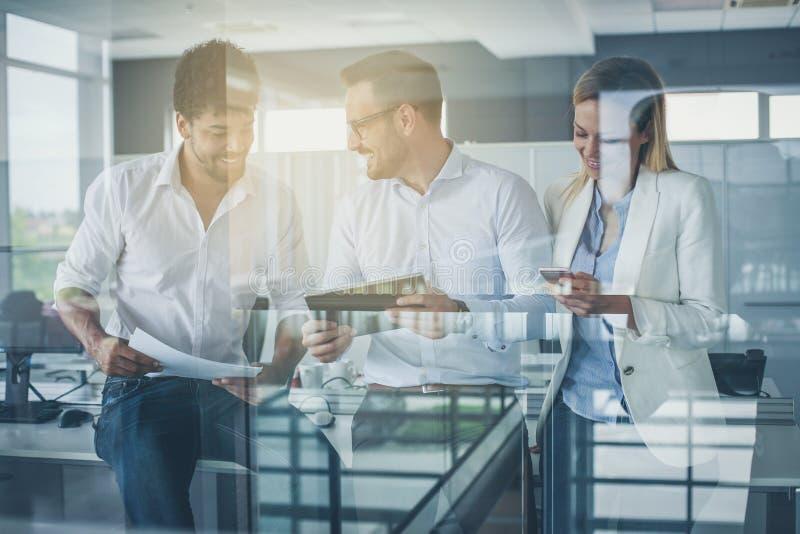 Бизнесмены в офисе имея переговор и используя technolo стоковое изображение