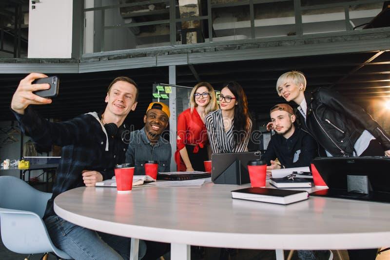 Бизнесмены в умной случайной носке обсуждают дела, используя ноутбук, выпивая кофе и усмехаясь делать промежутка времени стоковые фото
