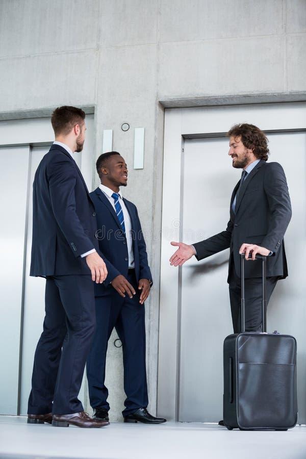 Бизнесмены говоря пока ждущ лифт стоковое фото rf