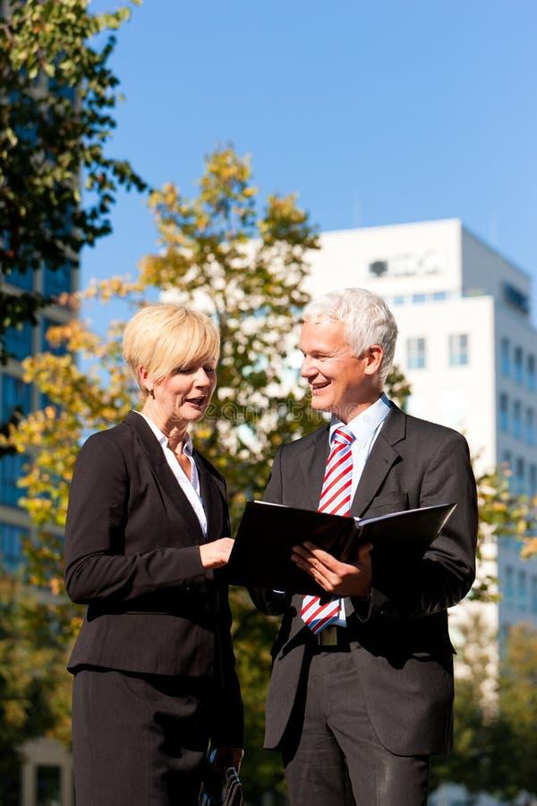 Бизнесмены говоря outdoors стоковое изображение