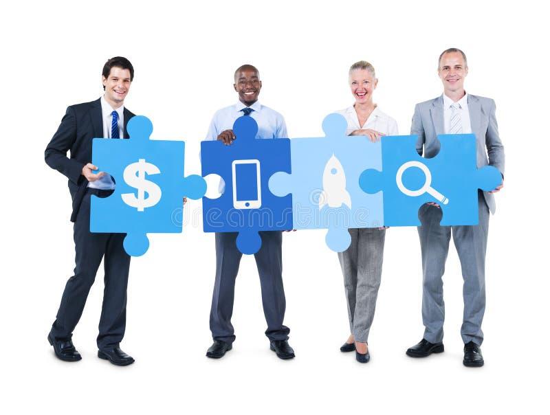 Бизнесмены держа головоломку соединяют различные значки стоковое изображение