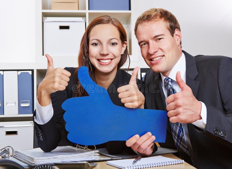 Бизнесмены держа много больших пальцев руки стоковые фото