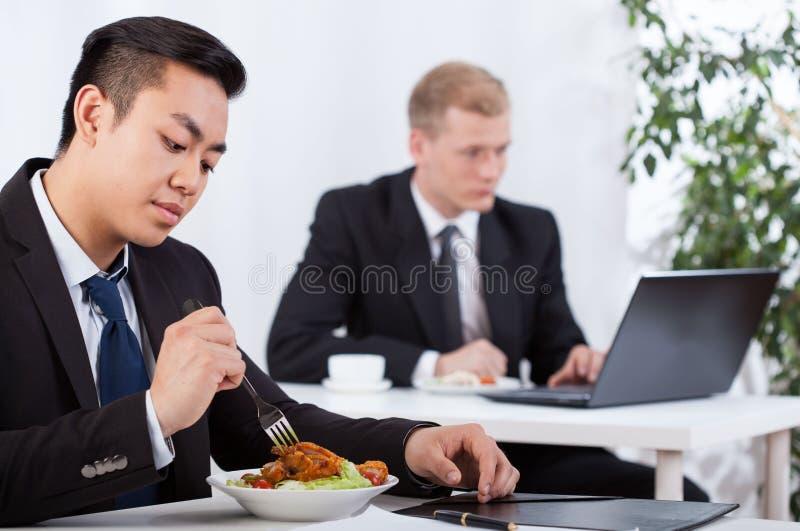 Бизнесмены есть здоровую еду в офисе стоковое фото