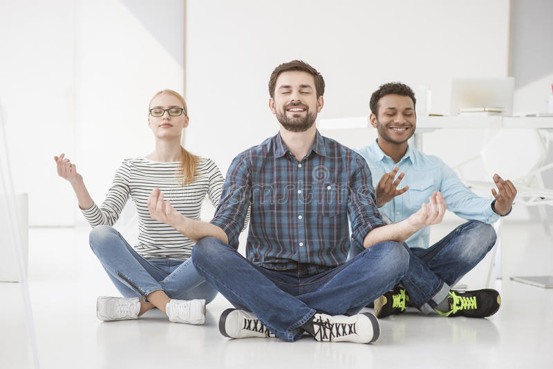 Бизнесмены делая йогу на поле в офисе стоковая фотография rf