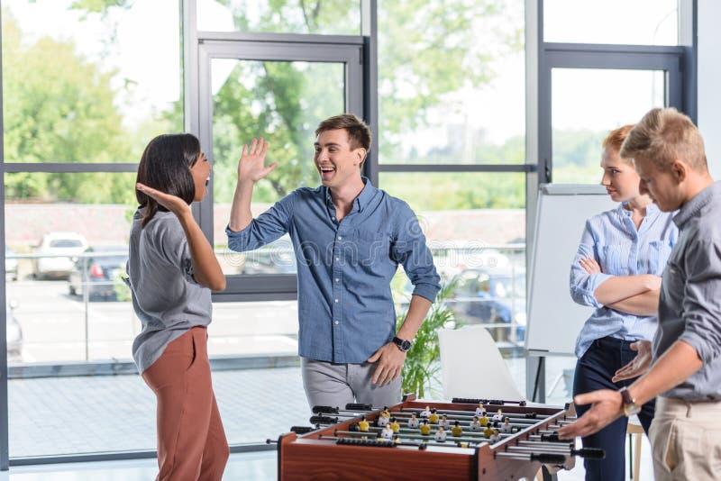 Бизнесмены играя футбол таблицы во время пролома стоковые фотографии rf