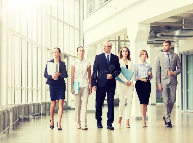 Бизнесмены идя вдоль офисного здания стоковые фото