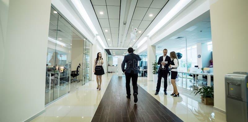 Бизнесмены идя в коридор офиса, бизнесмены c стоковые изображения rf