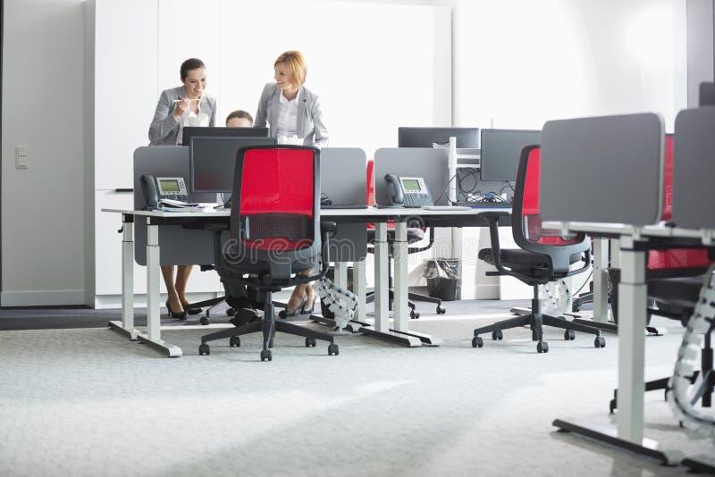 Бизнесмены имея обед пока использующ компьютер в офисе стоковые изображения