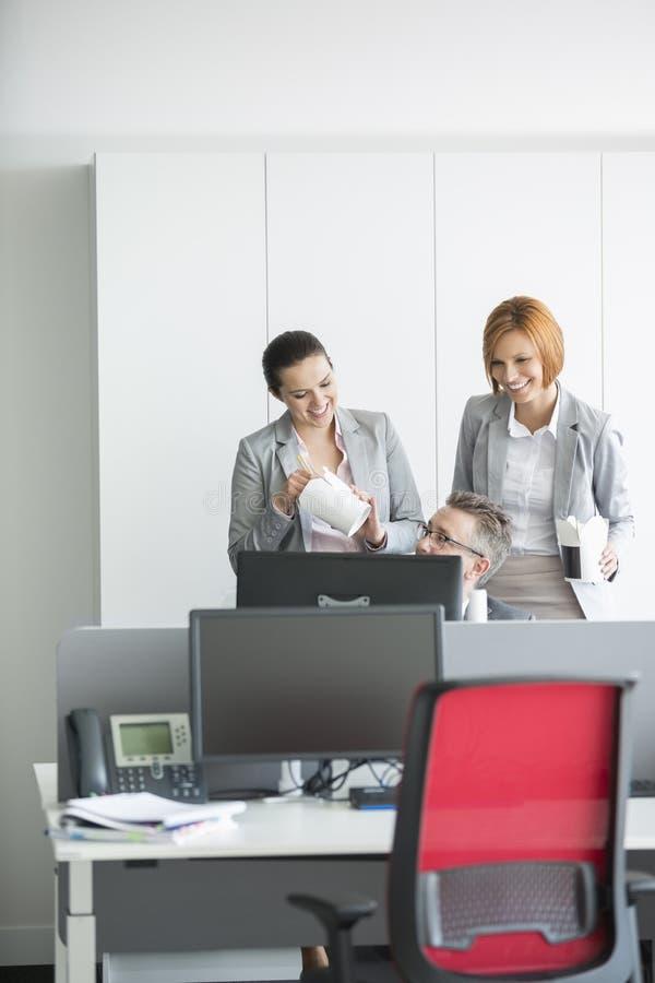Бизнесмены имея обед пока использующ компьютер в офисе стоковые изображения rf