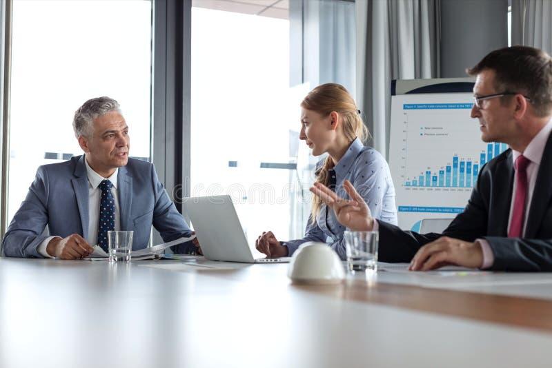 Бизнесмены имея обсуждение на таблице в комнате правления стоковое изображение rf