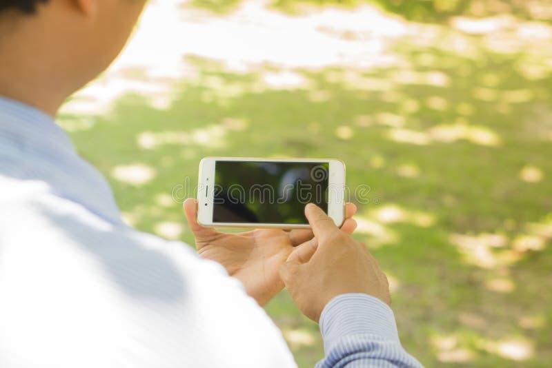 Бизнесмены используют smartphones для того чтобы побеседовать с клиентами стоковое фото