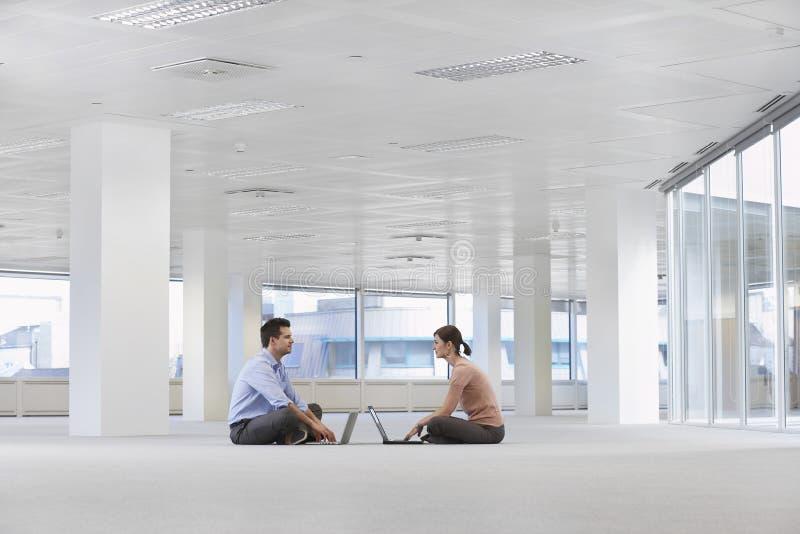 Бизнесмены используя компьтер-книжки в пустых размерах офиса стоковое изображение