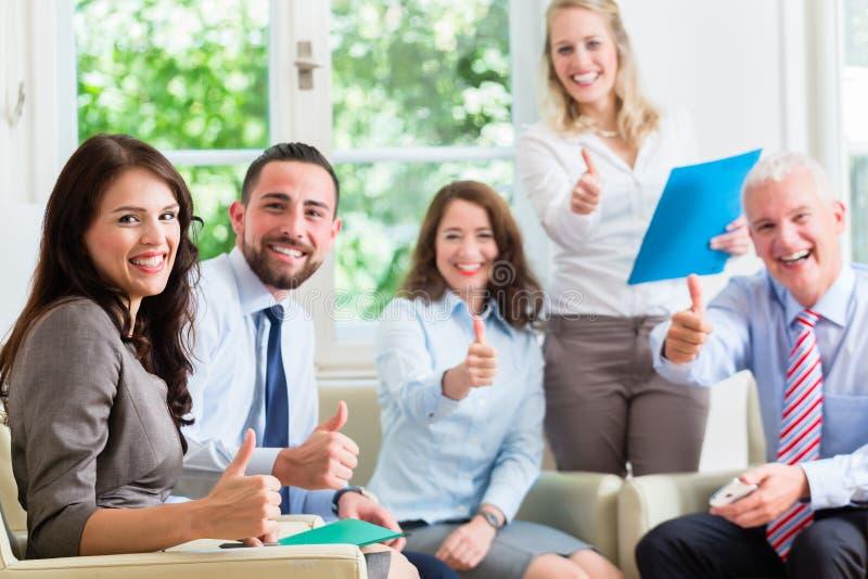 Бизнесмены и женщины в офисе имея успех стоковое изображение