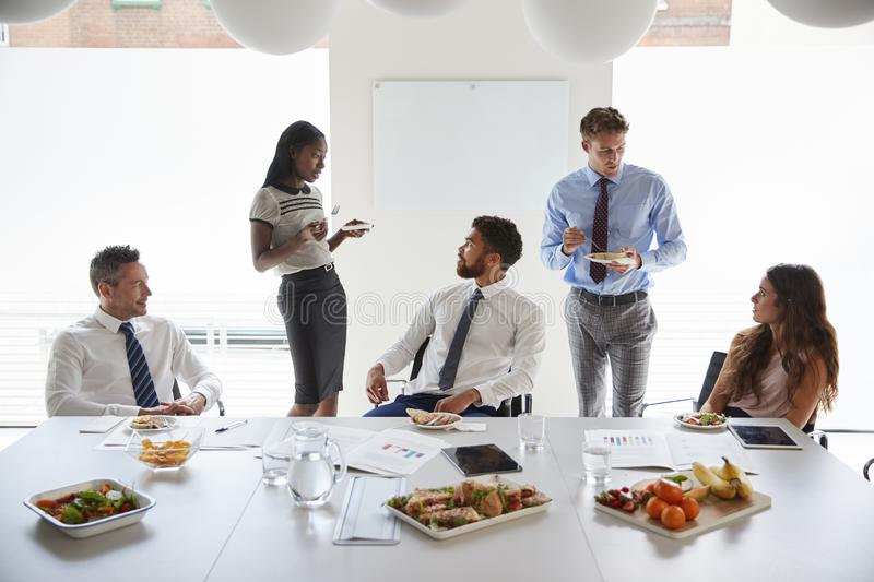 Бизнесмены и коммерсантки встречая в современном зале заседаний правления над рабочим обедом стоковые фото