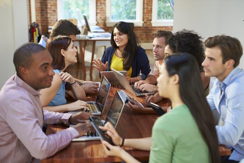 Бизнесмены и коммерсантки встречая для того чтобы обсудить идеи стоковые изображения rf