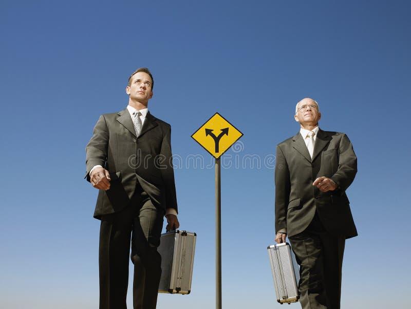 Бизнесмены идя за дорожным знаком стоковое изображение rf