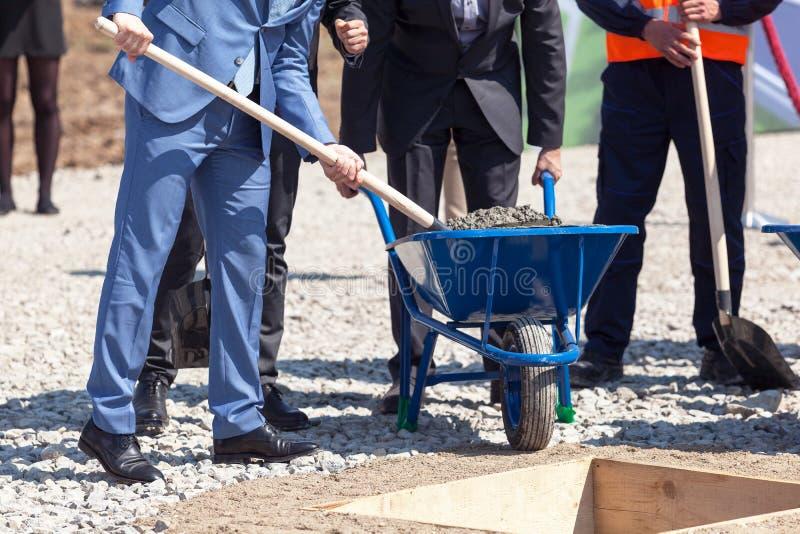 Бизнесмены на первом камне кладя церемонию для нового здания стоковые изображения