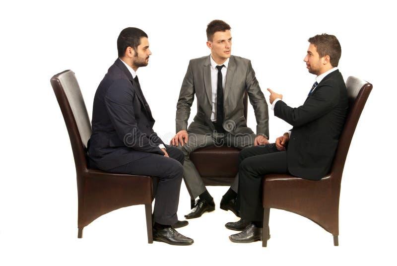 Бизнесмены на стулах имея переговор стоковое фото rf