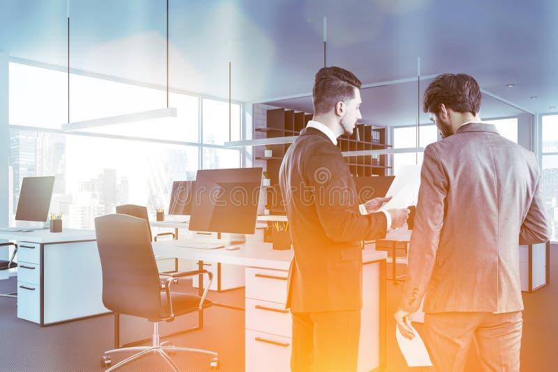 Бизнесмены обсуждают документы в белом офисе стоковые изображения rf
