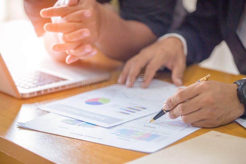 Бизнесмены обсуждая диаграммы и диаграммы показывая res стоковое фото