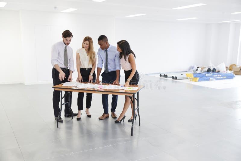 4 бизнесмены обсуждая дизайн интерьера офиса стоковое изображение rf