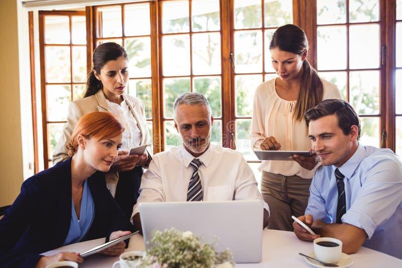 Бизнесмены обсуждая над ноутбуком на таблице стоковое фото