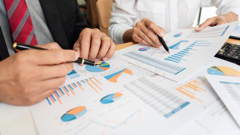 Бизнесмены обсуждая проект на встрече указывать объясняющ его диаграммы идеи и коллегу диаграммы на работу имея встречу для стоковое фото