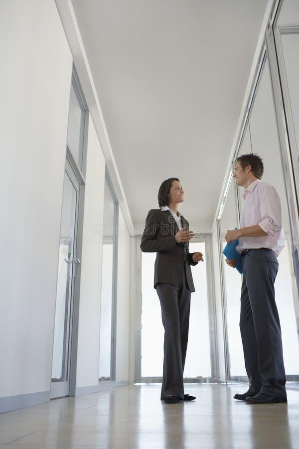 Бизнесмены обсуждая в коридоре стоковое изображение