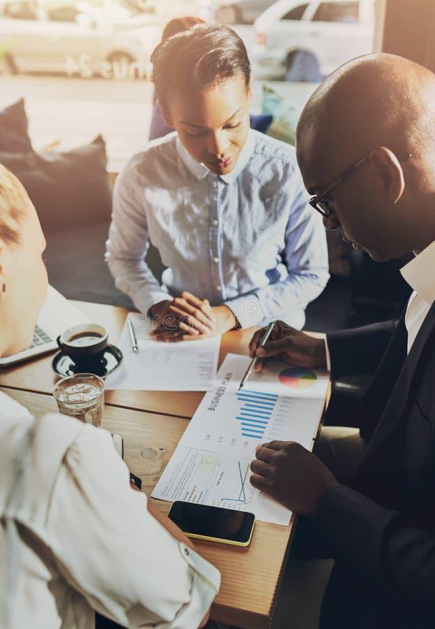 Бизнесмены обсуждая диаграммы стоковая фотография