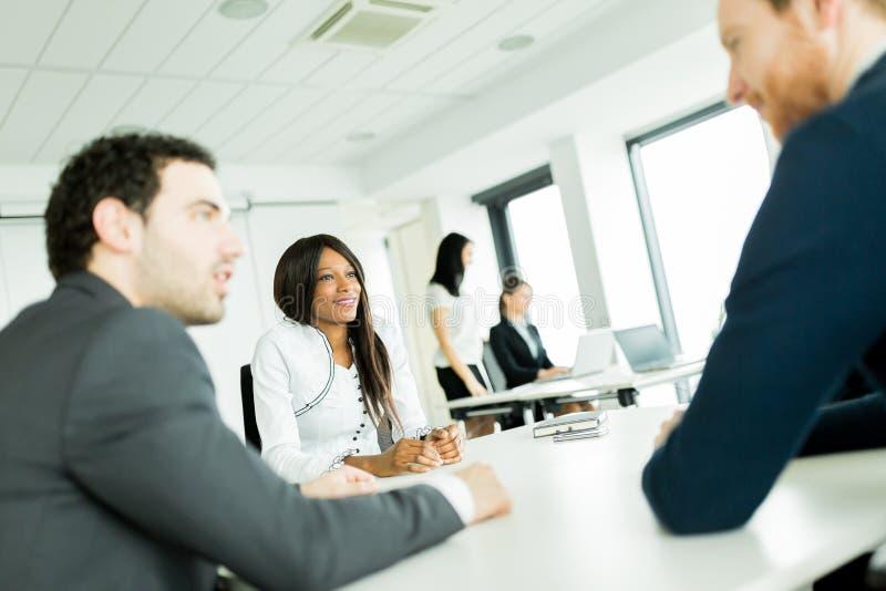 Бизнесмены обсуждая и коллективно обсуждать на белом столе внутри стоковое изображение