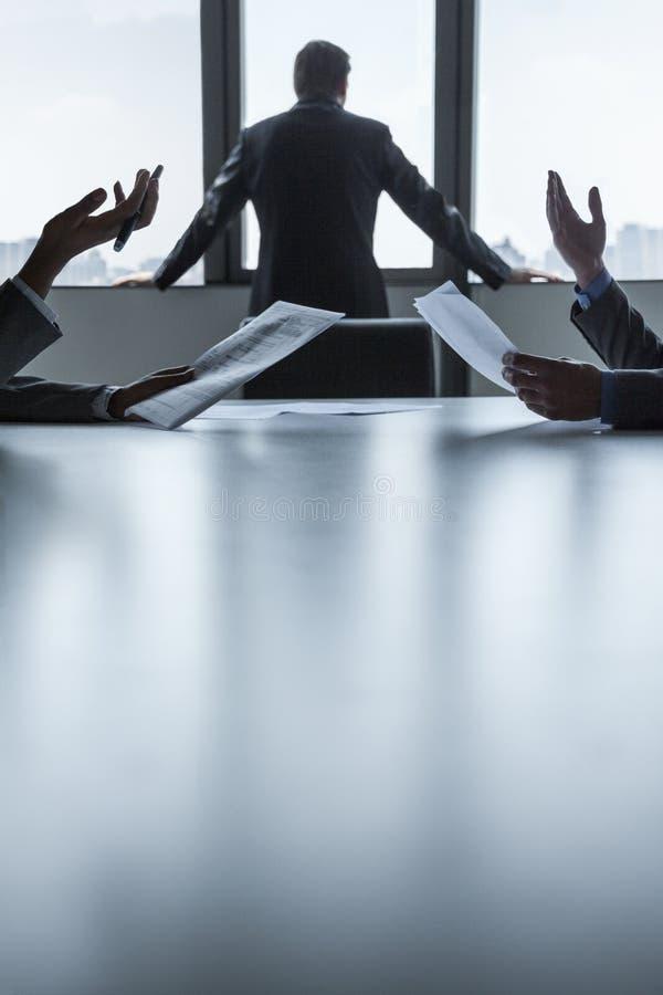 2 бизнесмены обсуждая и показывать над таблицей пока другое смотрит вне окно, руками только стоковое фото rf