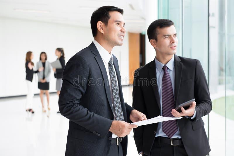 Бизнесмены обсуждая работу в коридоре офисного здания стоковое изображение rf