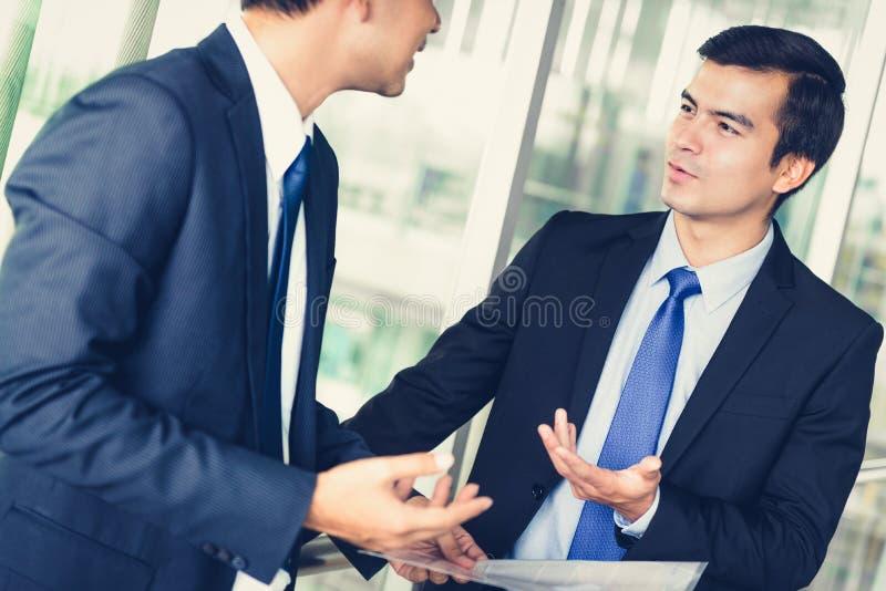 Бизнесмены обсуждая работу на коридоре офисного здания стоковое изображение rf