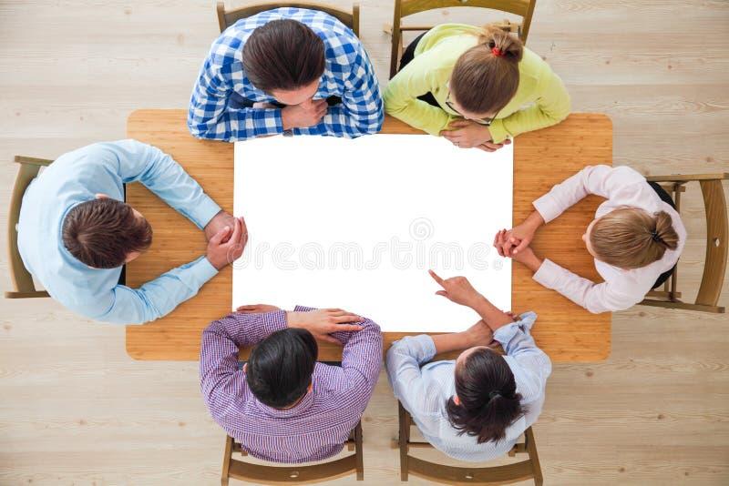 Бизнесмены объединяются в команду с чистым листом бумаги стоковые изображения