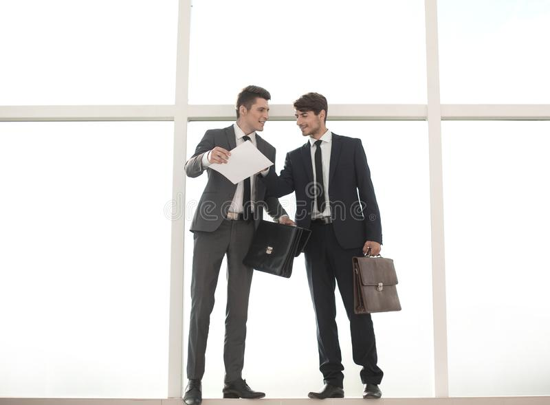 Бизнесмены при кожаные портфели стоя около офиса стоковое фото rf