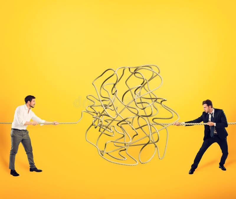 Бизнесмены пробуют разрешить запутанную веревочку Концепция партнерства стоковая фотография rf