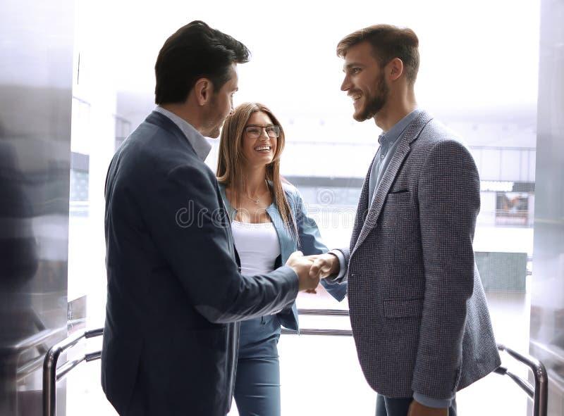 Бизнесмены протягивая вне их руки для рукопожатия стоковое изображение