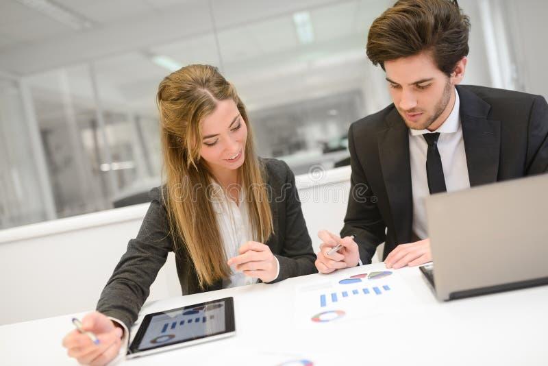 Бизнесмены работая вокруг таблицы в современном офисе стоковая фотография