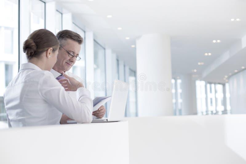 Бизнесмены работая на перилах в офисе стоковые изображения rf
