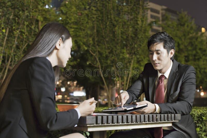 Бизнесмены работая пока имеющ обедающий стоковое изображение
