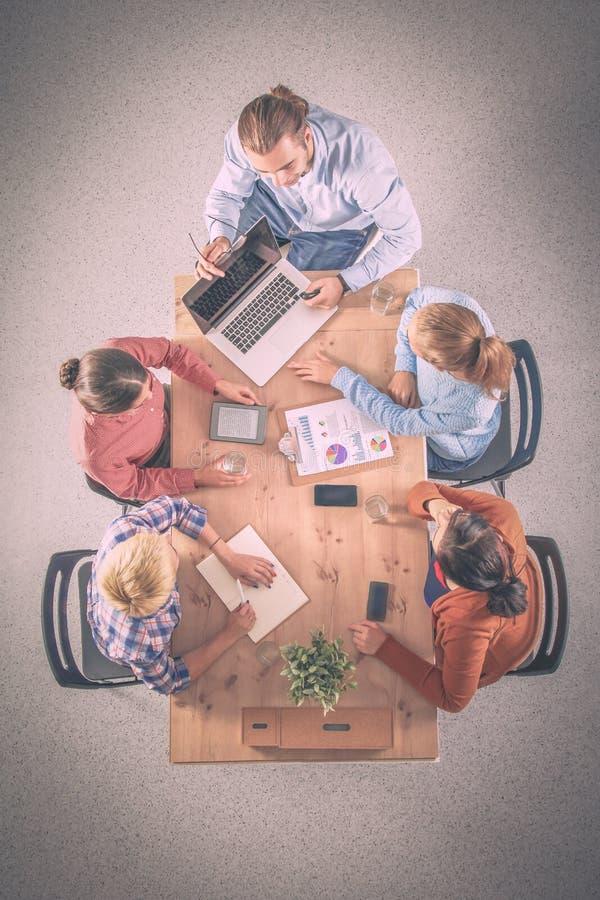 Бизнесмены сидя и обсуждая на встрече, в офисе стоковое изображение rf