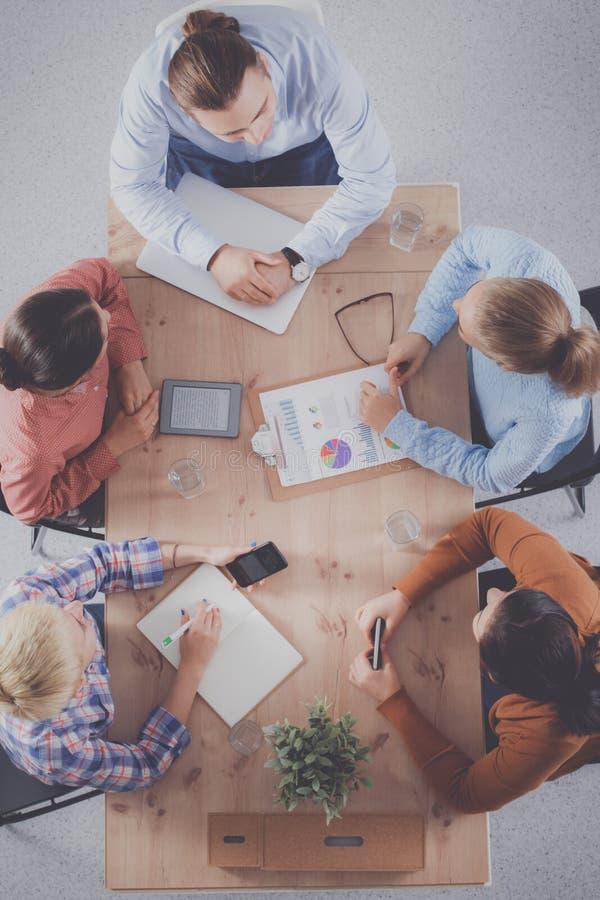 Бизнесмены сидя и обсуждая на встрече, в офисе стоковая фотография